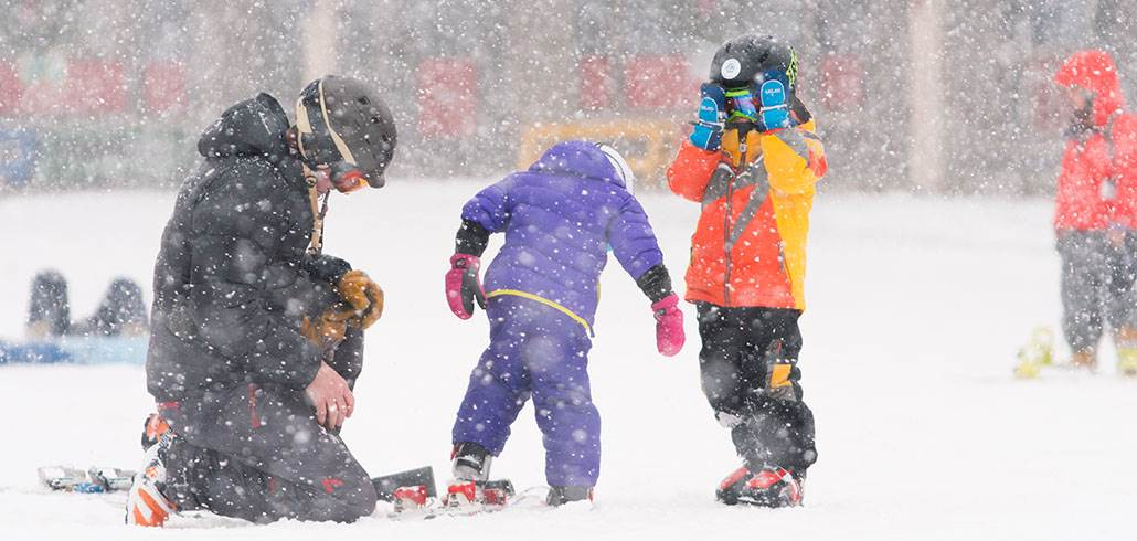 Kids putting on skis in snow